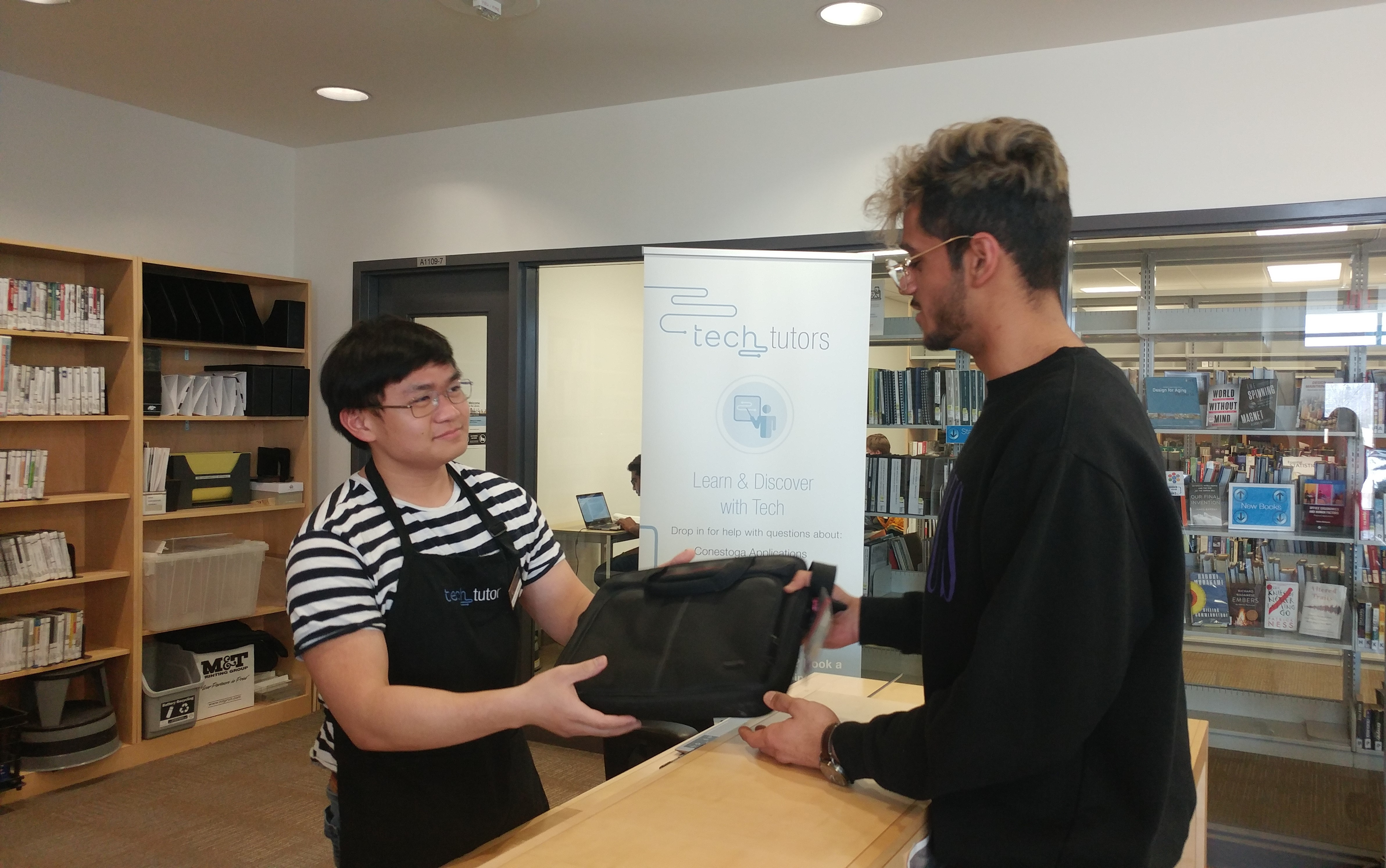 a staff member handing a computer to a student