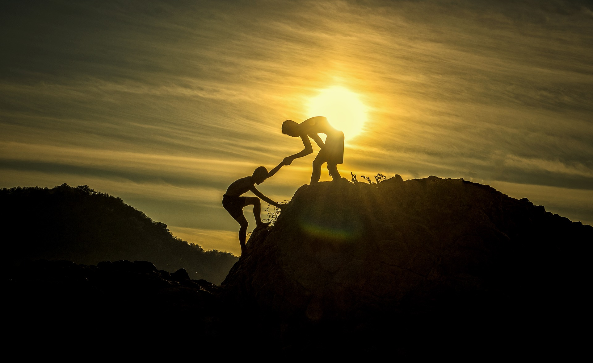 Person reaching out a hand to help another person reach the top of the mountain