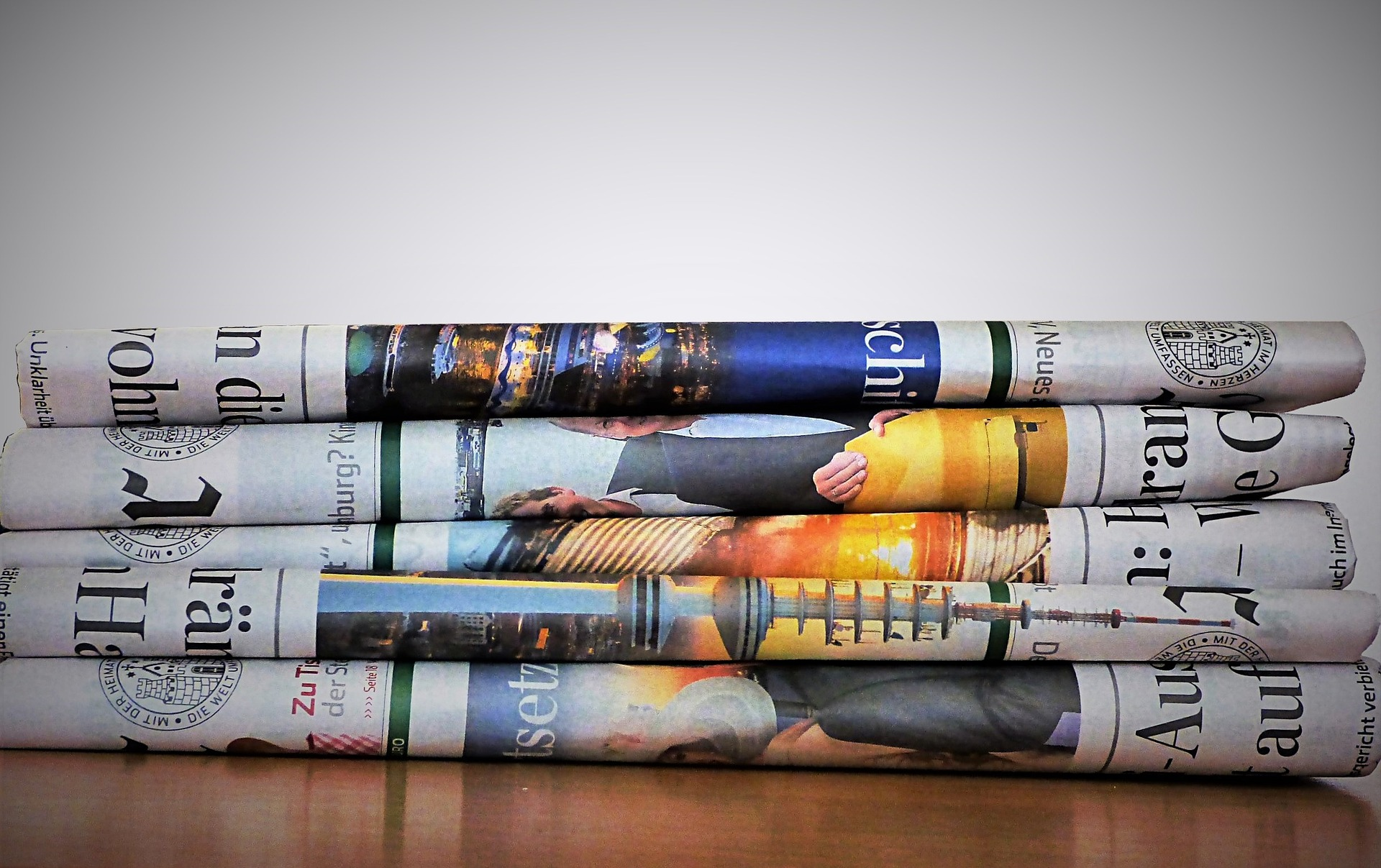 pile of four newspapers on a table