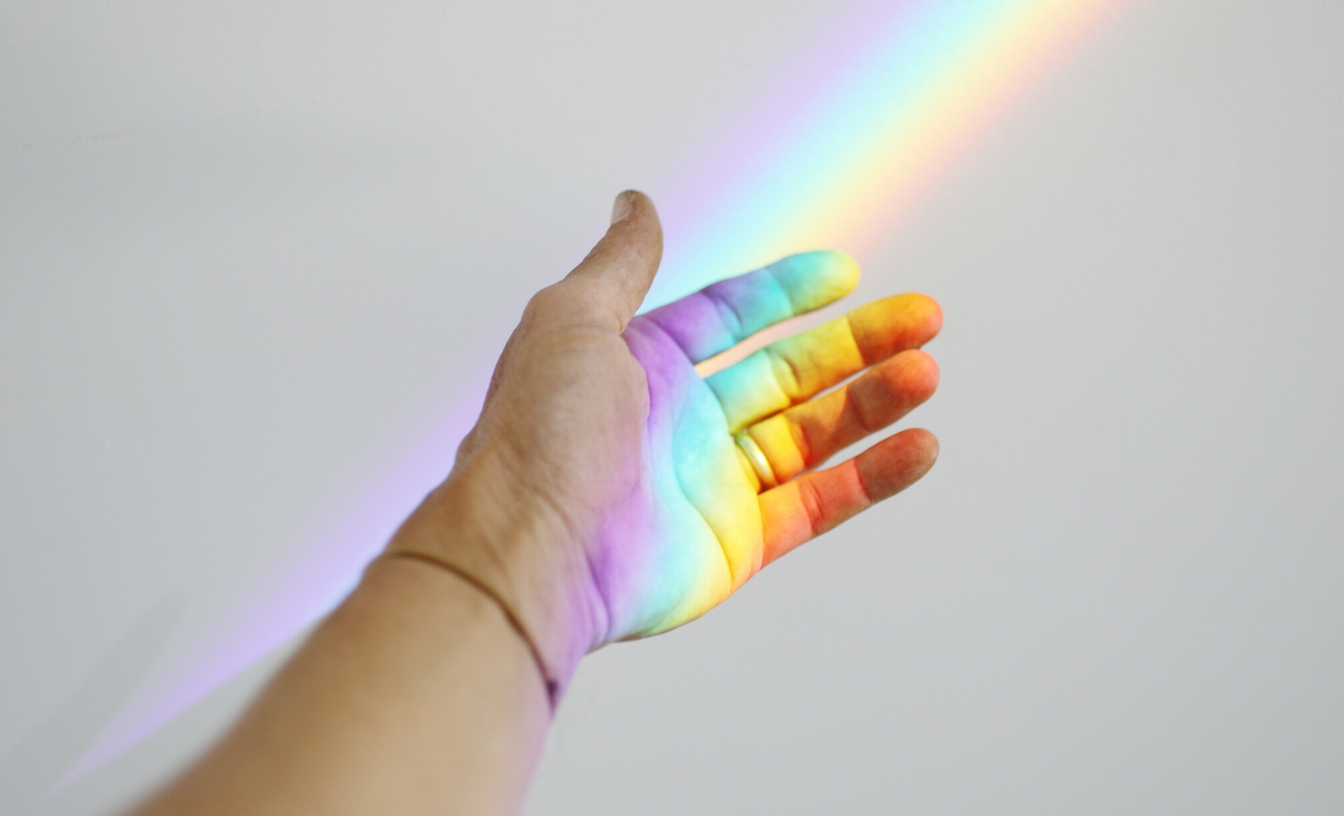 A hand reaching for a rainbow