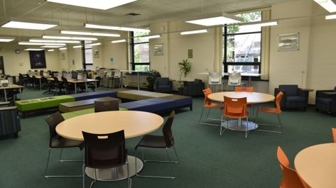 Learning space with tables and seating. Computer carrels in the background