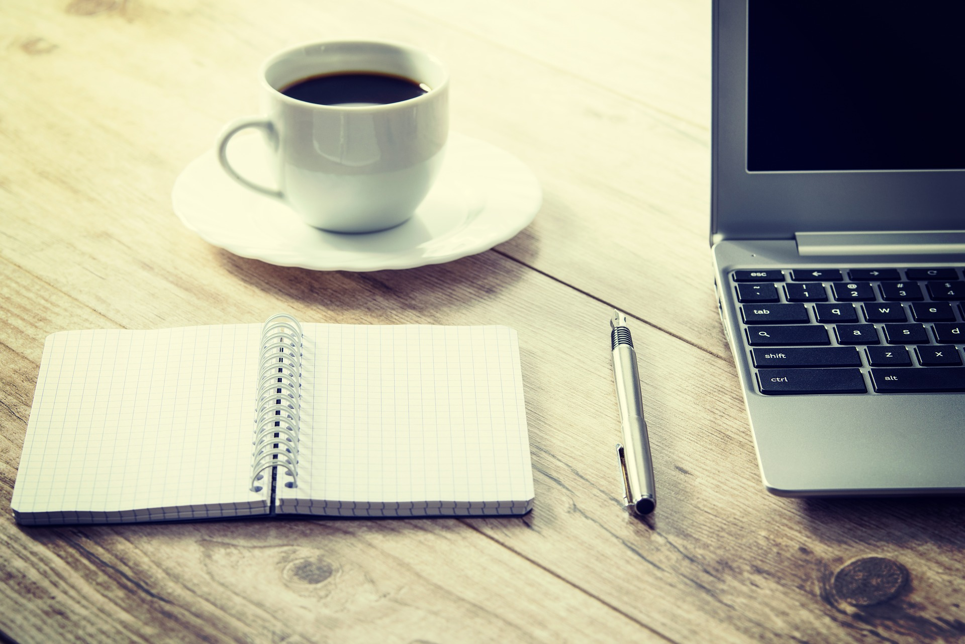 A coffee cup, notebook and laptop on a wooden desk