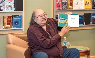 Photo left: Alan Syliboy reads his new book, <i>Mi'kmaw Waisisk / Mi'kmaw Animals</i>