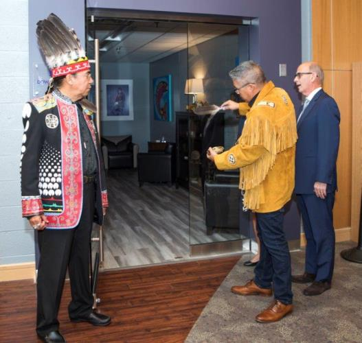Stephen Augustine and Graham Marshall perform a traditional smudging ceremony as David Dingwall observes