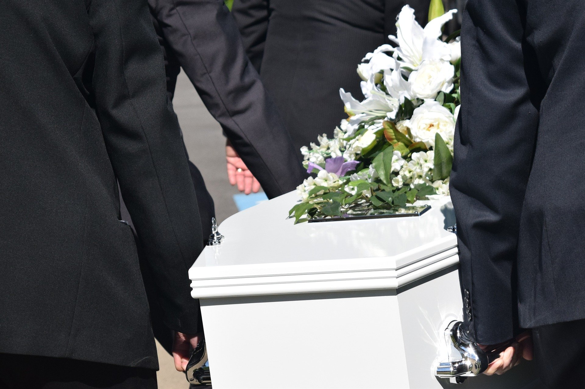 Pallbearers carrying a white casket adorned with flowers