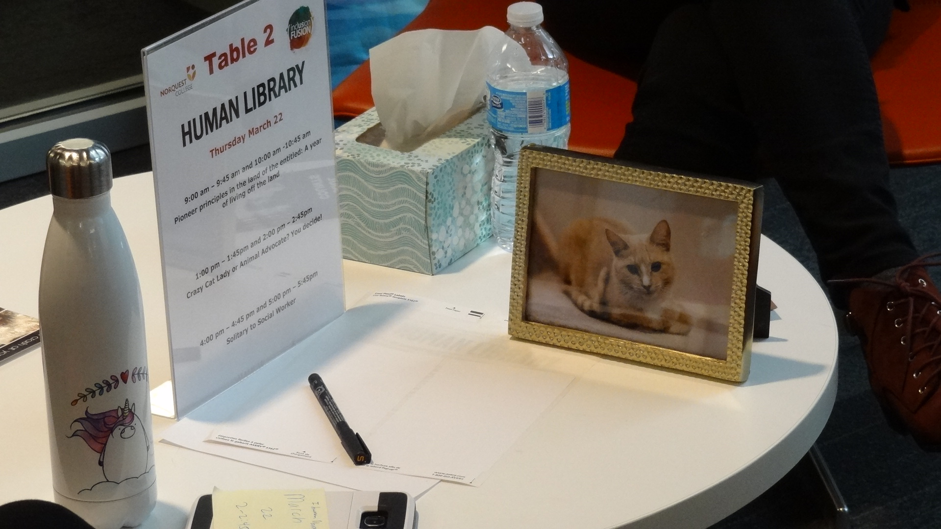 Photo of a table with a poster for the human library and a framed picture of a cat