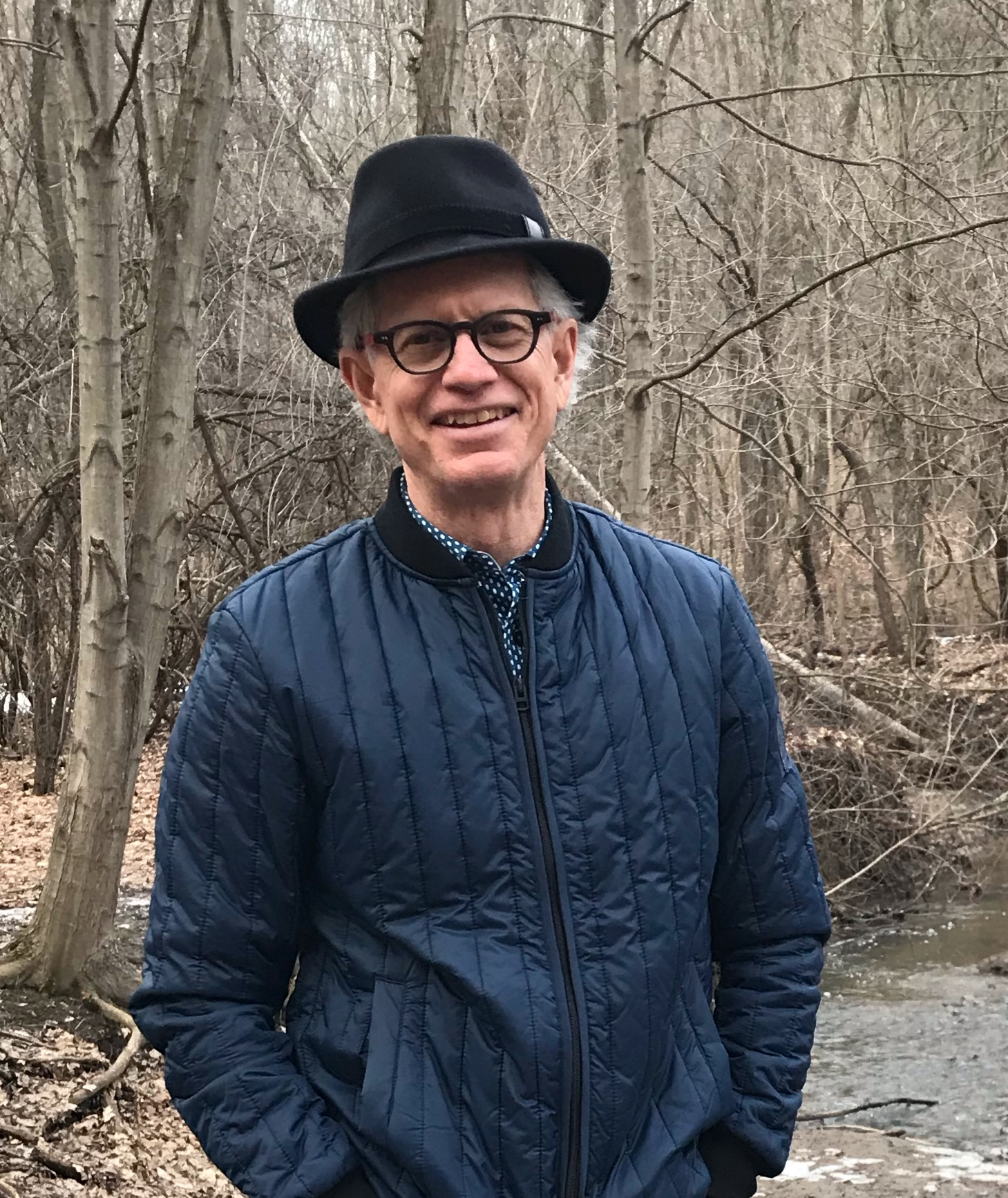 photograph of Daniel Coleman wearing a blue jacket and black hat, standing in front of barren trees in the winter.