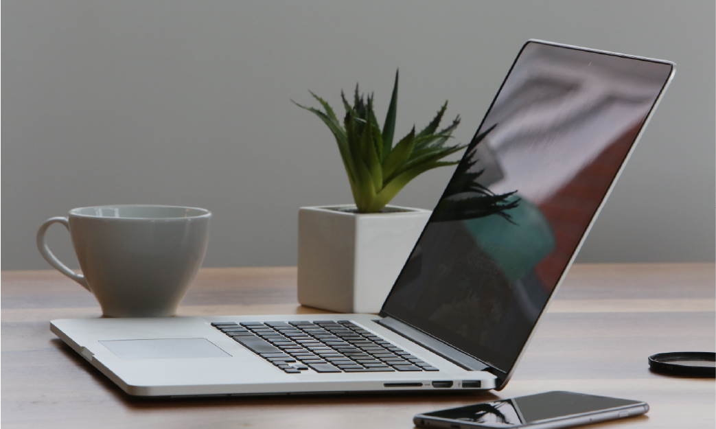 Laptop beside a plant and coffee cup