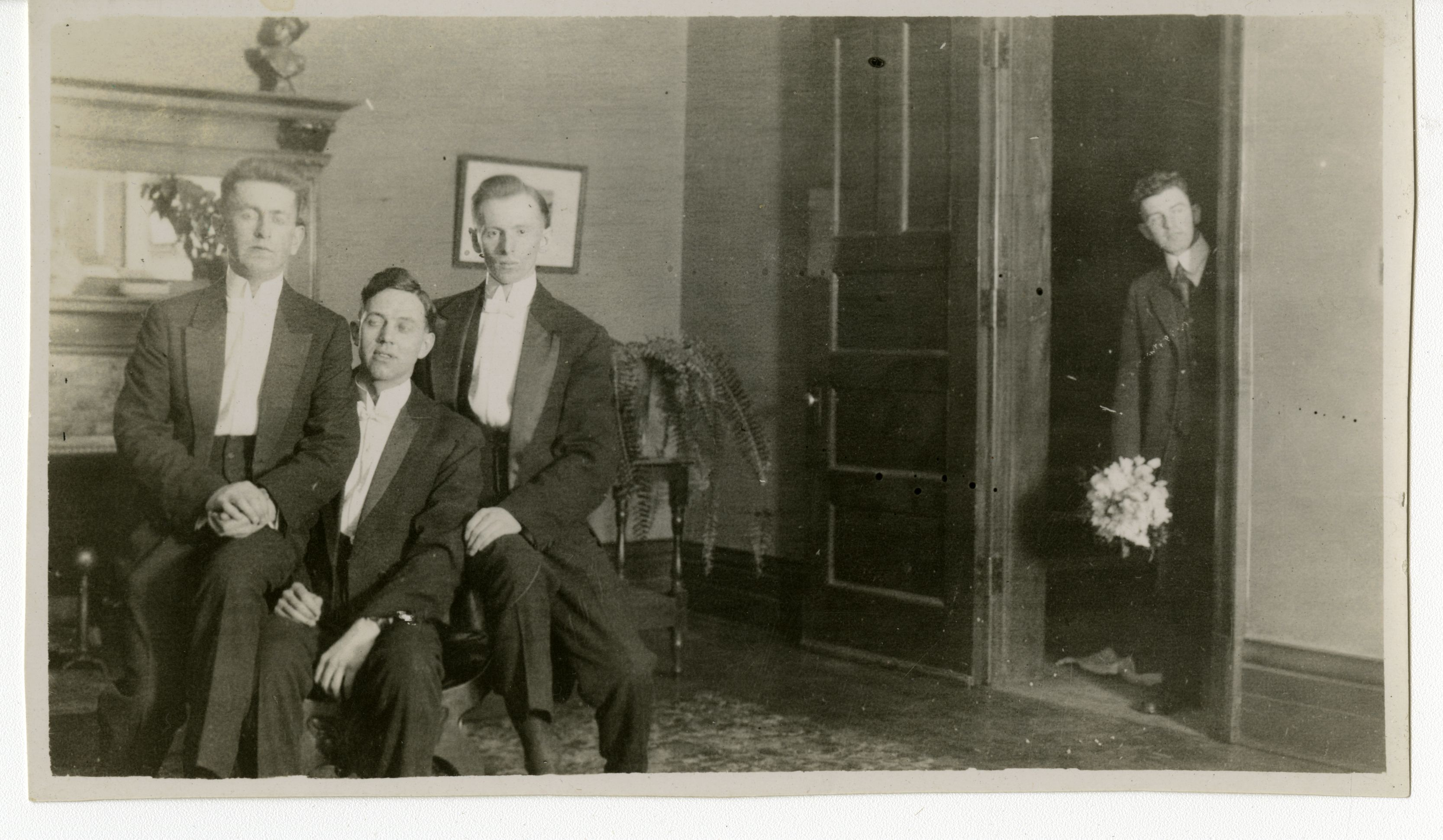 Three men sitting together at the left while another man is at the door holding a bouquet of flowers. All of them are wearing suits. They appear to be in a parlour room rather than on a stage.