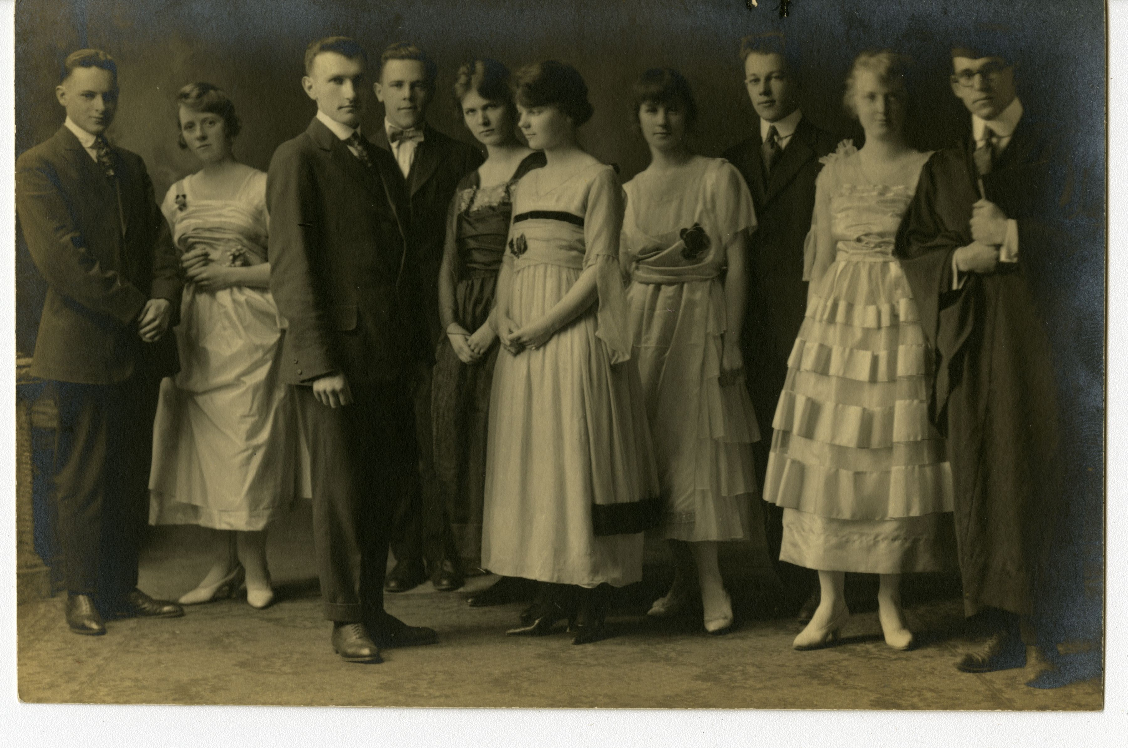 A group of 10 men and women standing together in costumes. The men wear suits while the women wear evening dresses typical of the time period.