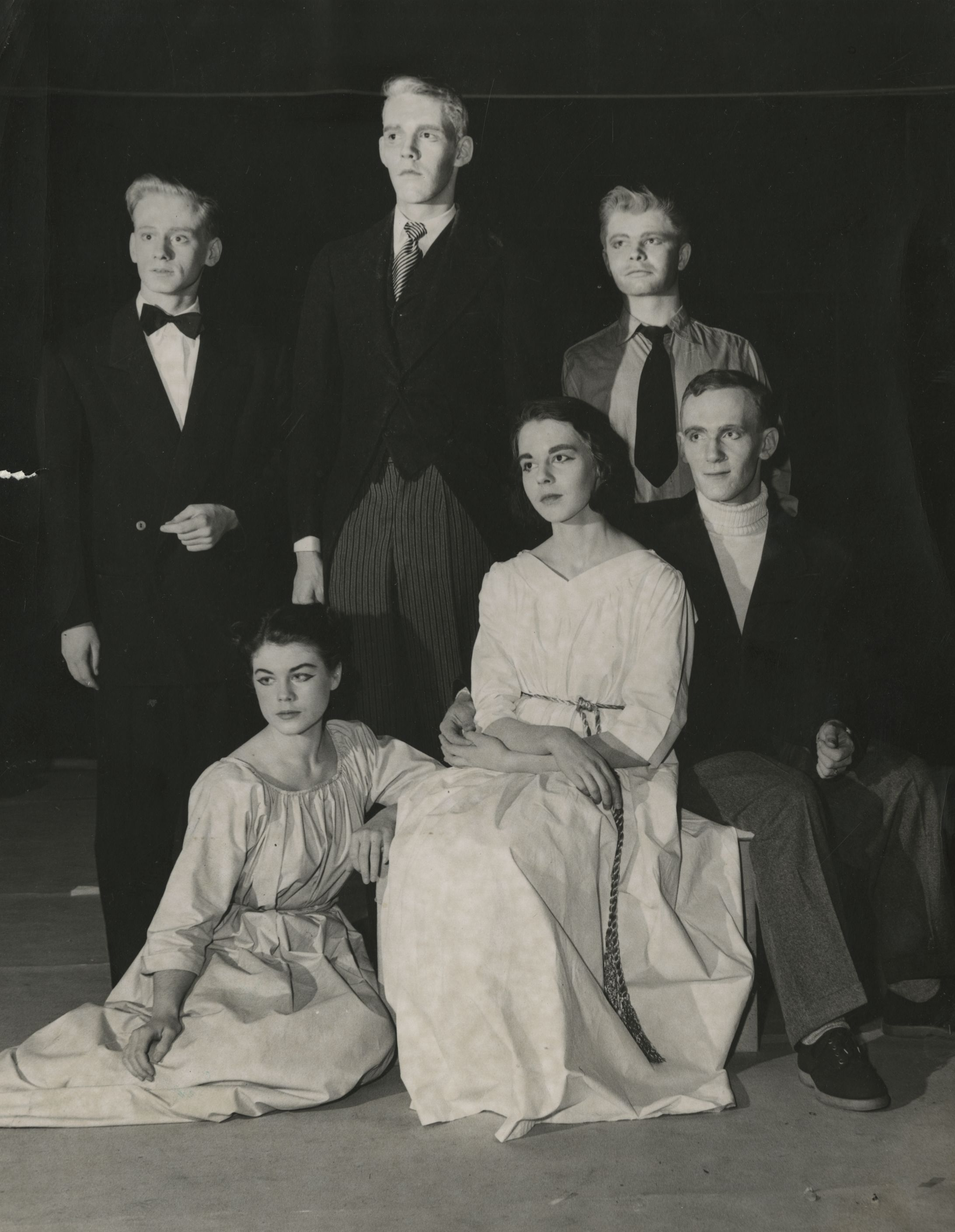 Six cast members sitting or standing together on stage in costume. The women wear simple white dresses while the men are wearing suits and tuxedos.