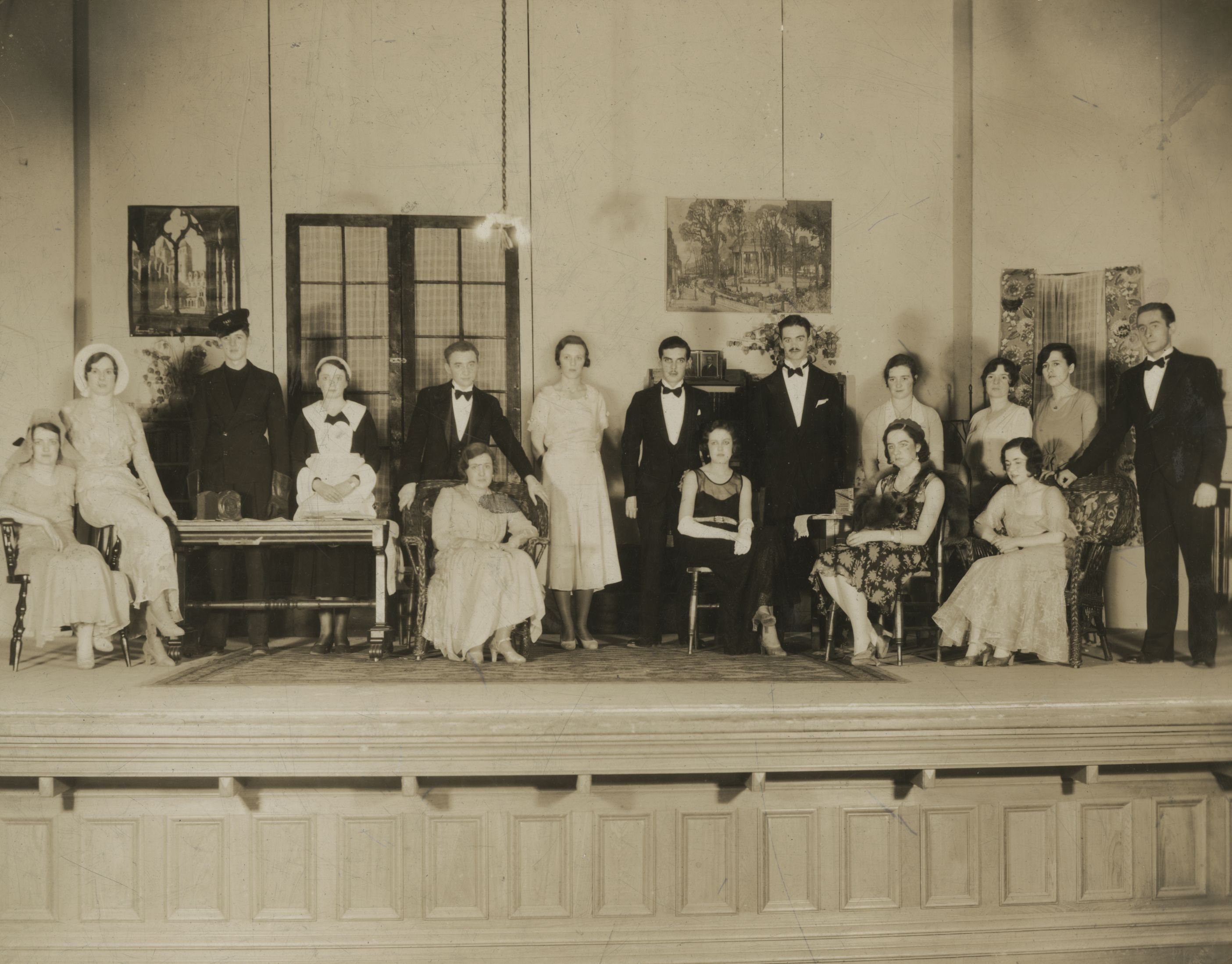 A group of sixteen men and women stand or sit on stage in costumes. Most of them are wearing tuxedos or evening dresses typical of the period, with the exception of one man dressed in a soldier's uniform and one woman dressed as a maid. The stage has been decorated with chairs, tables, a fake window, and posters on the walls.