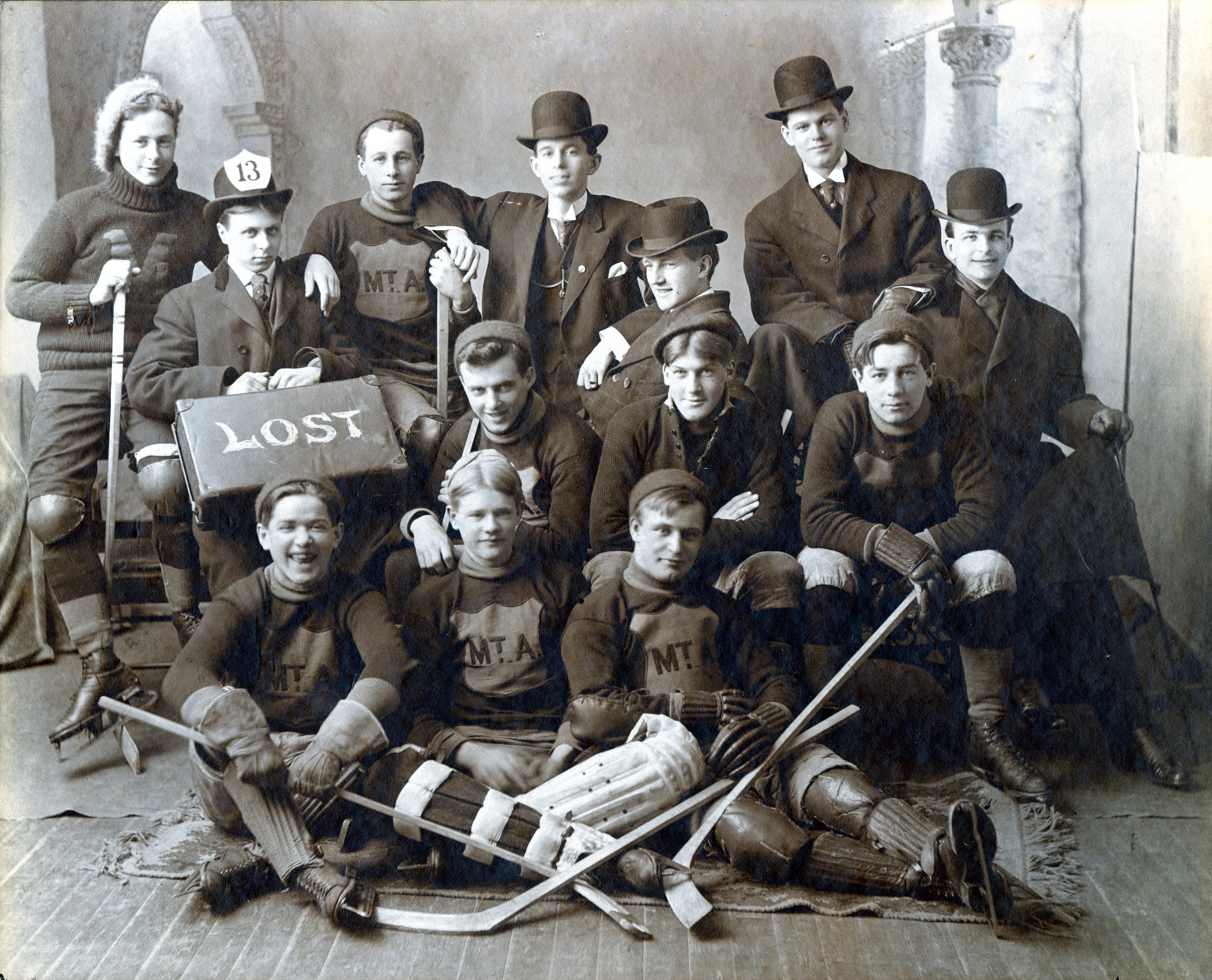 Group picture of members of the hockey team in their sports uniform with additional costume props.
