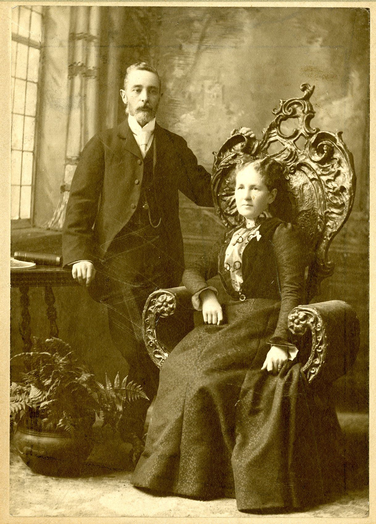 Mary sitting in an ornate chair while Andrew stands beside her.