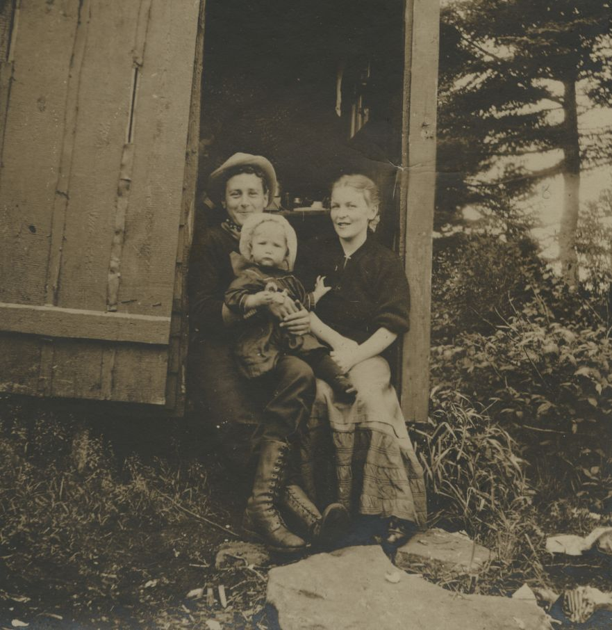 Ralph and Marguerite sitting in a doorway of a cabin with their daughter on Ralph's knees