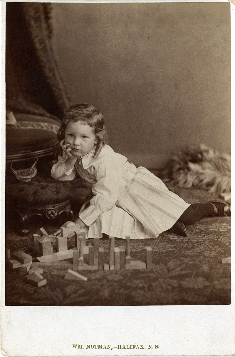 Winthrop Pickard Bell as a child sitting on the ground of a photographer's studio in a white dress. In front of him are wooden playing blocks.