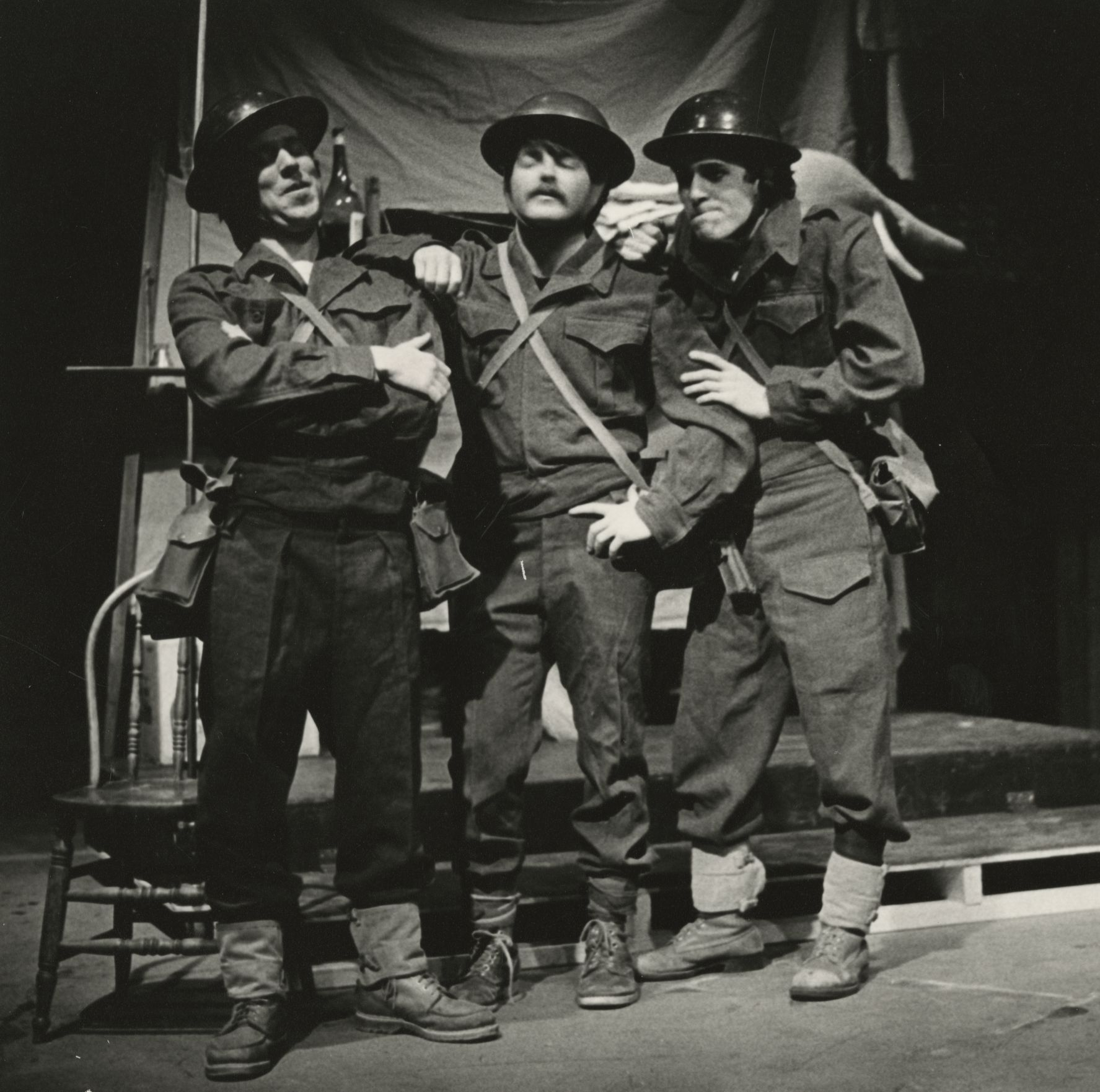 Three men standing together on stage wearing military uniforms. The stage is decorated with drop sheet, a table and chair, and liquor bottles.