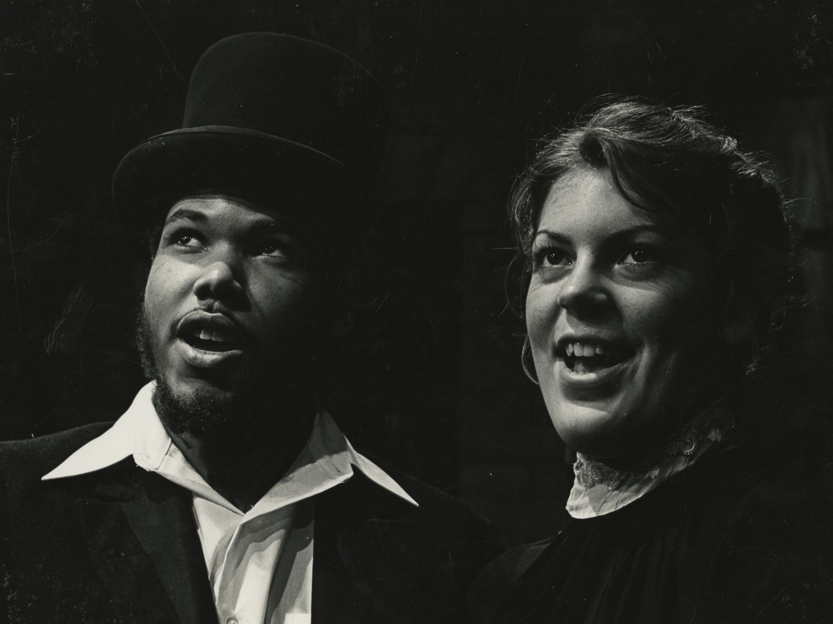 A man and a woman singing together. They are both wearing Victorian period costumes.