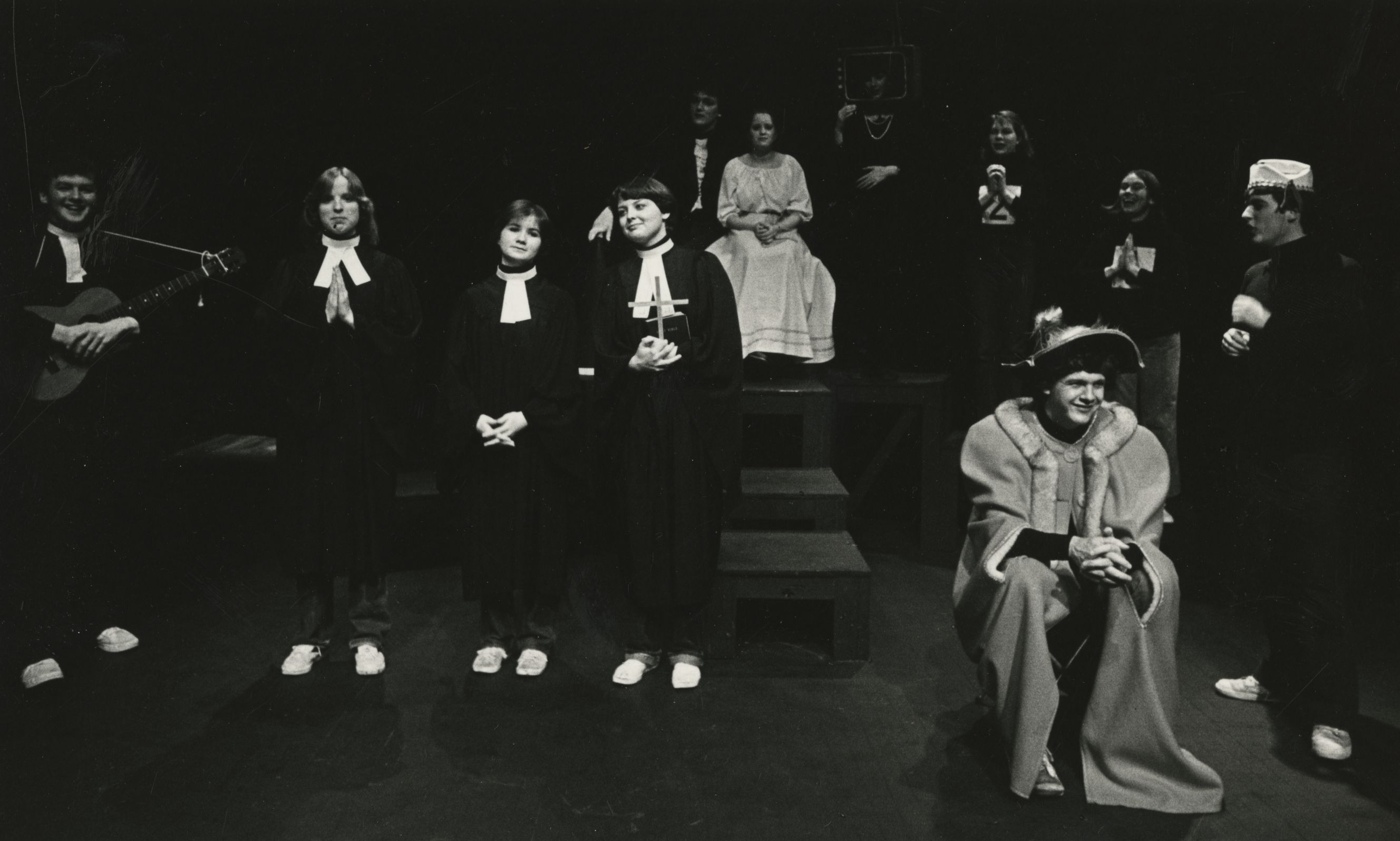 Eleven men and women on stage. They are wearing a variety of costumes, including a few dressed as clergy and one as royalty. One person in the background appears to be dressed as a television. The man standing to the left is holding a guitar.