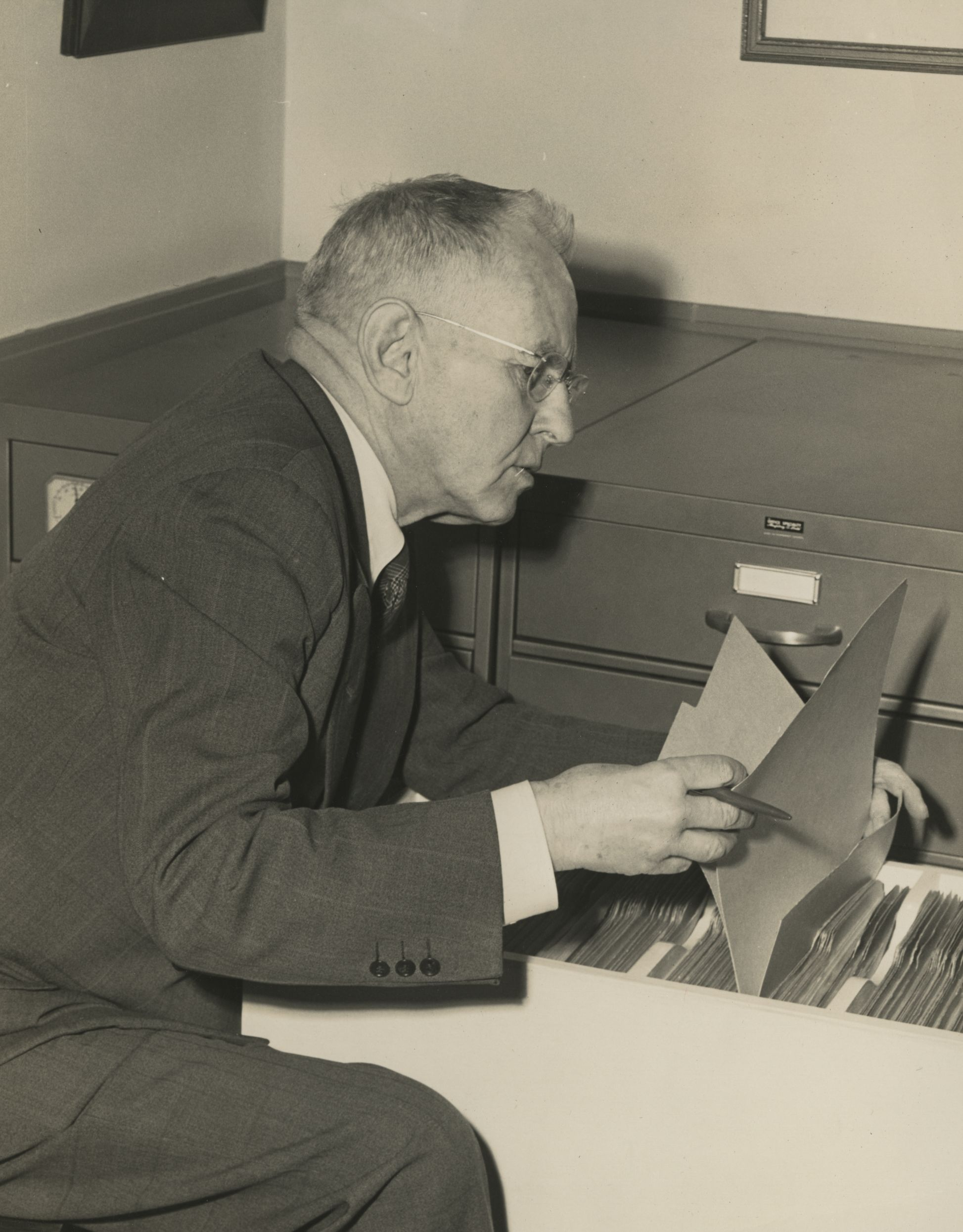 Winthrop Pickard Bell leaning in front of a filing cabinet looking through files.