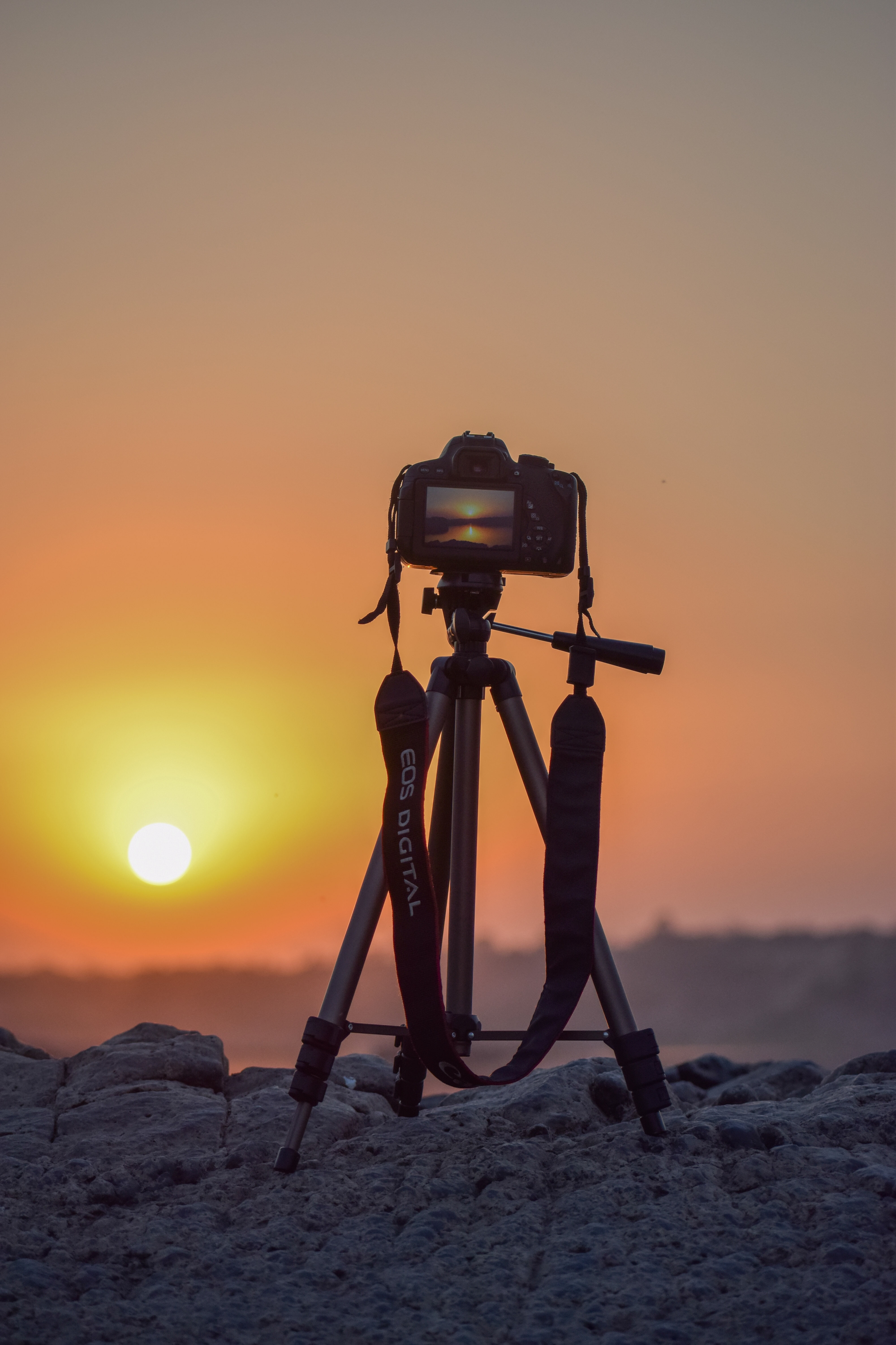 Image of a camera on a tripod in front of a sunset.