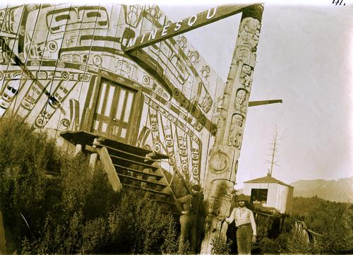 Black and white photo of a man standing at the base of a totem pole outside a building covered with indigenous art.