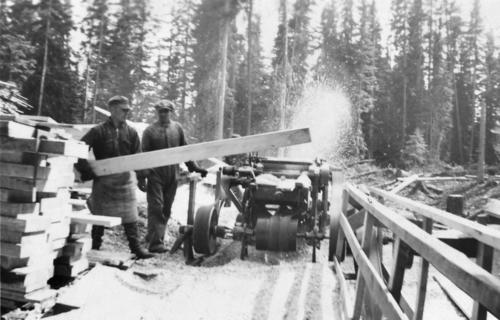 Workers cutting timber with portable sawmill
