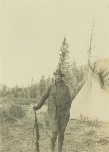 2000.19.1.55 - Prentiss Gray standing with rifle in hand in front of a teepee