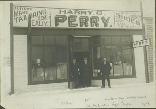 2002.7.1.3 - Mr. Moore, HGT Perry & Parr Brown standing in front of Harry G. Perry's Tailor Shop, Fort George