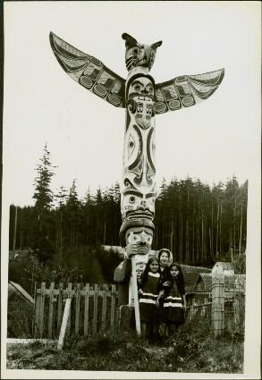 Three young, First Nations girls stand in front of a Memorial Pole