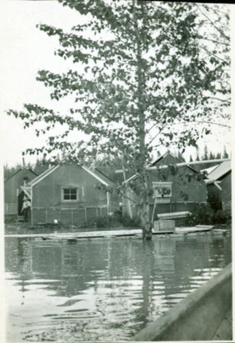 Photograph depicts lane in front of tent buildings flooded with water.