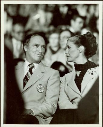 2009.6.1.371 - Canada Winter Games, Brandon, MB - Prime Minister Pierre Trudeau and Iona Campagnolo sit in navy and pale blue uniforms in crowded auditorium or arena at the opening of the games
