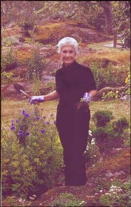 2009.6.1.693 - Iona Campagnolo holding a trowel and weeds in Terrace Gardens, Government House, Victoria, BC