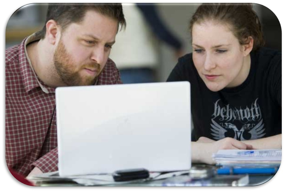 Picture of two students looking at a computer