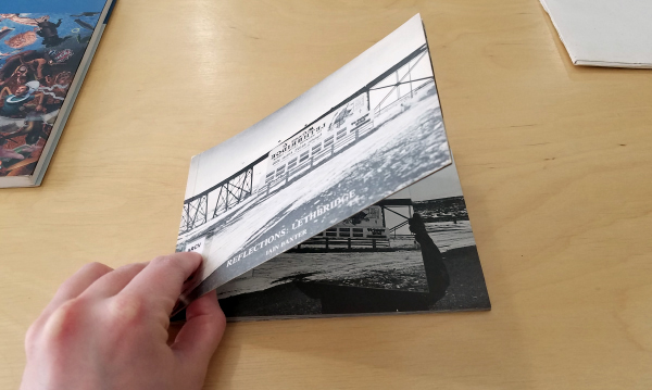 A person's hand opening an artists' book, the cover of which shows a black and white photograph of a train bridge in Lethbridge. Two more books sit on the desk in the background.
