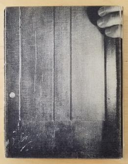 "The back cover of Michael Snow's ""Cover to Cover."" A black and white photo of a dark door that has a hand holding it from the upper right corner."
