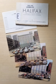 3 of 7 postcards showing a Halifax building on the corner of Granville and Buckingham Streets on different days. Stripes on the building's six columns change by one color each day.