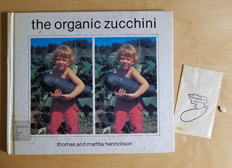 A seed pouch, zucchini seed, and book with cover showing two photos of a child in a garden holding a large zucchini.