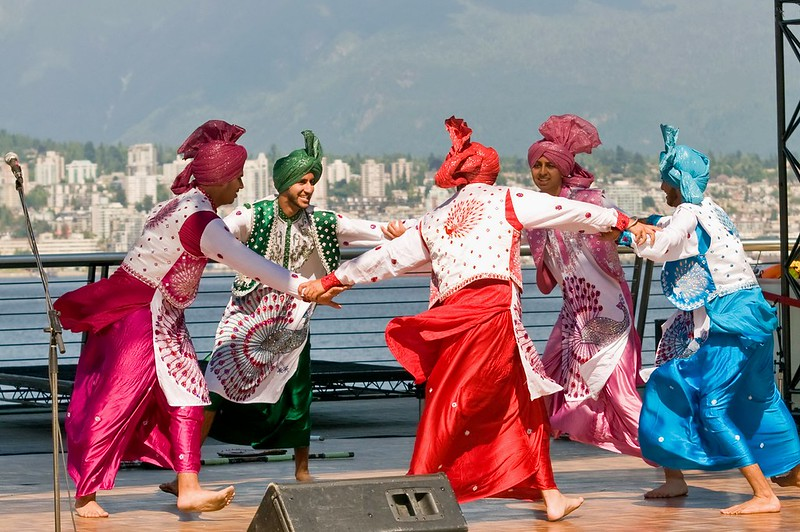 Five male bhangra dancers in traditional clothing dance in a circle with the Vancouver skyline in the background.