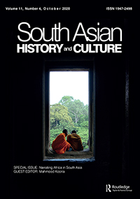 Asian monks crouch in a window overlooking trees