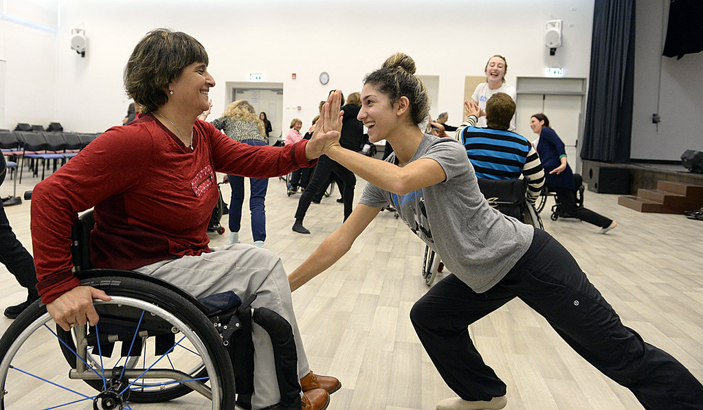 Image of two people dancing: one in a wheelchair, the other facing them.