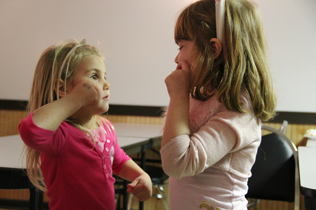 Two children facing each other, learning sign language