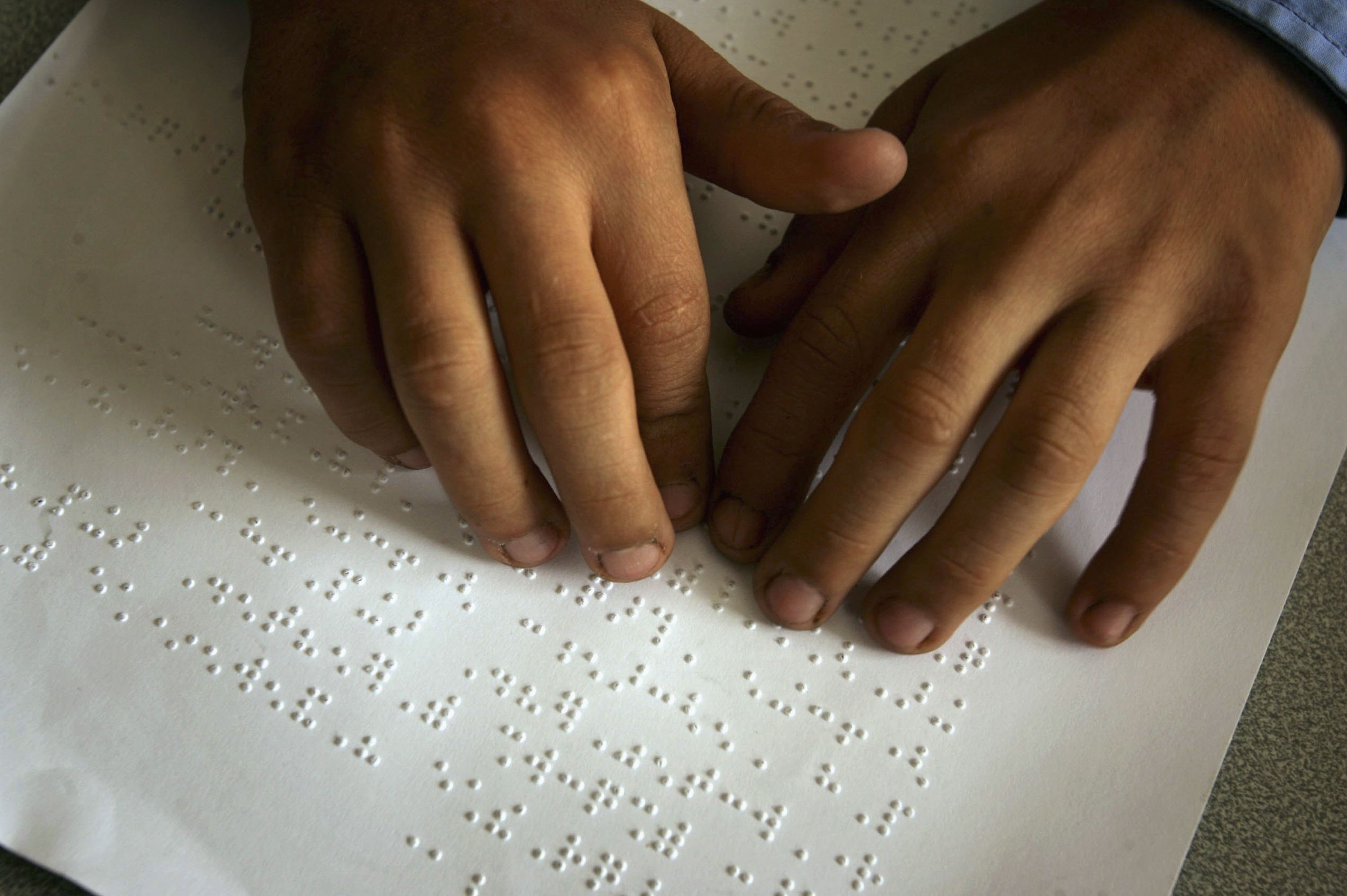 Two hands on a page written in braille