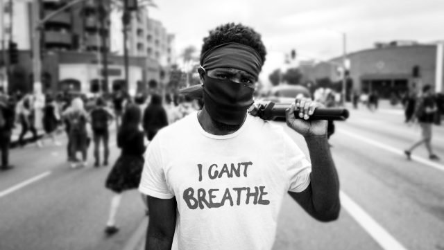 """Black and white picture of a Black person facing the camera. The person is wearing a face mask and a white shirt with """"I can't breathe"""" is written. Behind the person is a blurry, busy street."""