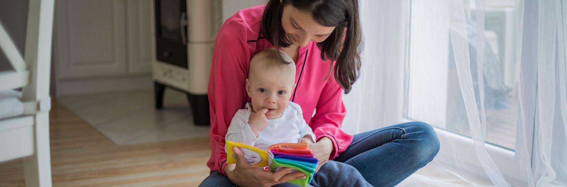 Une femme lit un livre à un bébé.