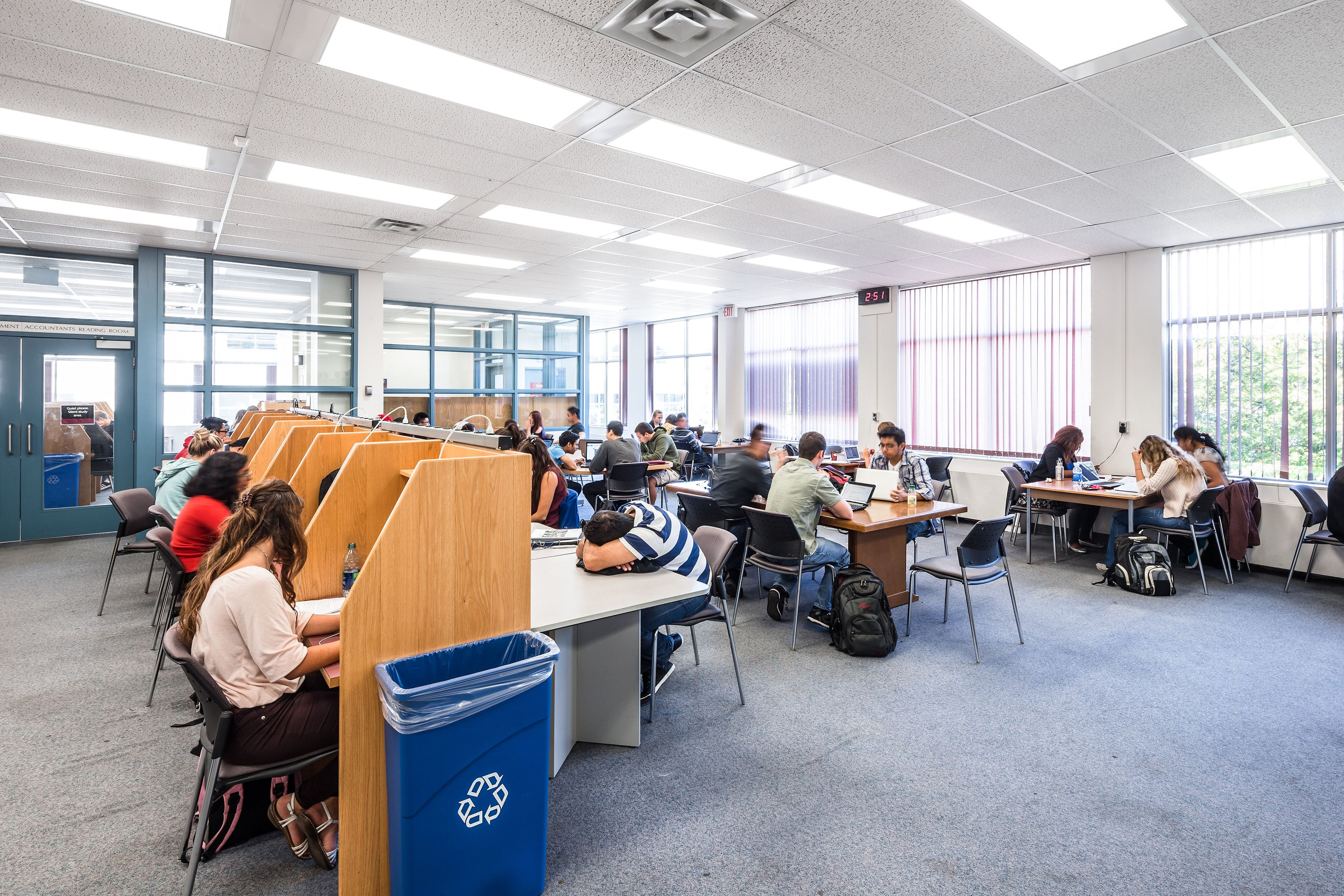 Photo of students studying in the now closed Innis Library's silent study room, carrels, open table area, and near windows