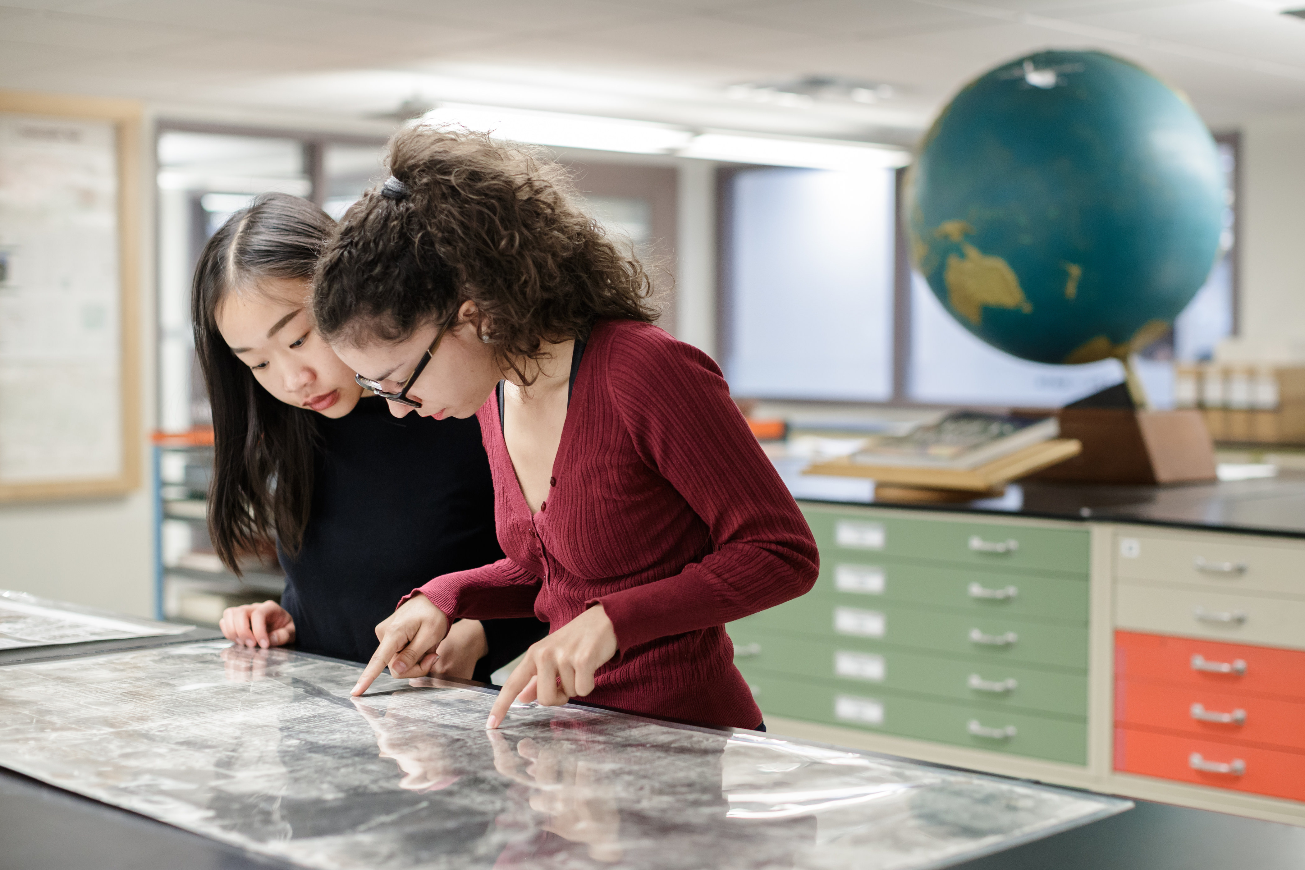 Photo of two students examining maps on map cabinets in McMaster Library's Maps, Data, GIS Centre