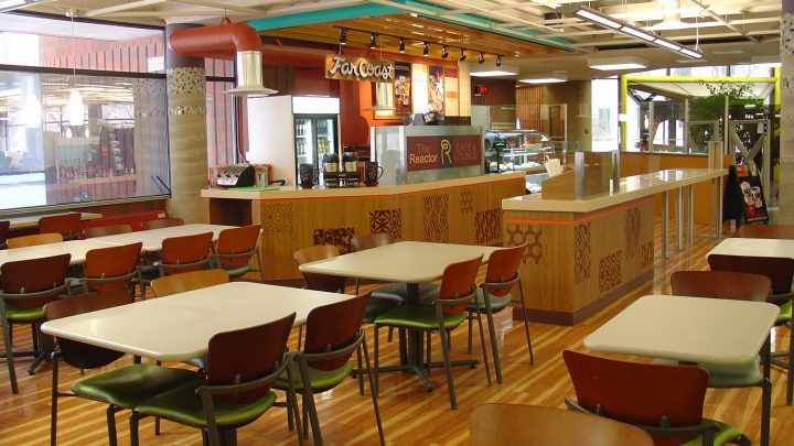 Photo of the Reactor Cafe with food display cases, coffee machines, beverage refrigerator, tables and chairs, and counter space. It is located on the main level of H.G. Thode Science and Engineering Library.