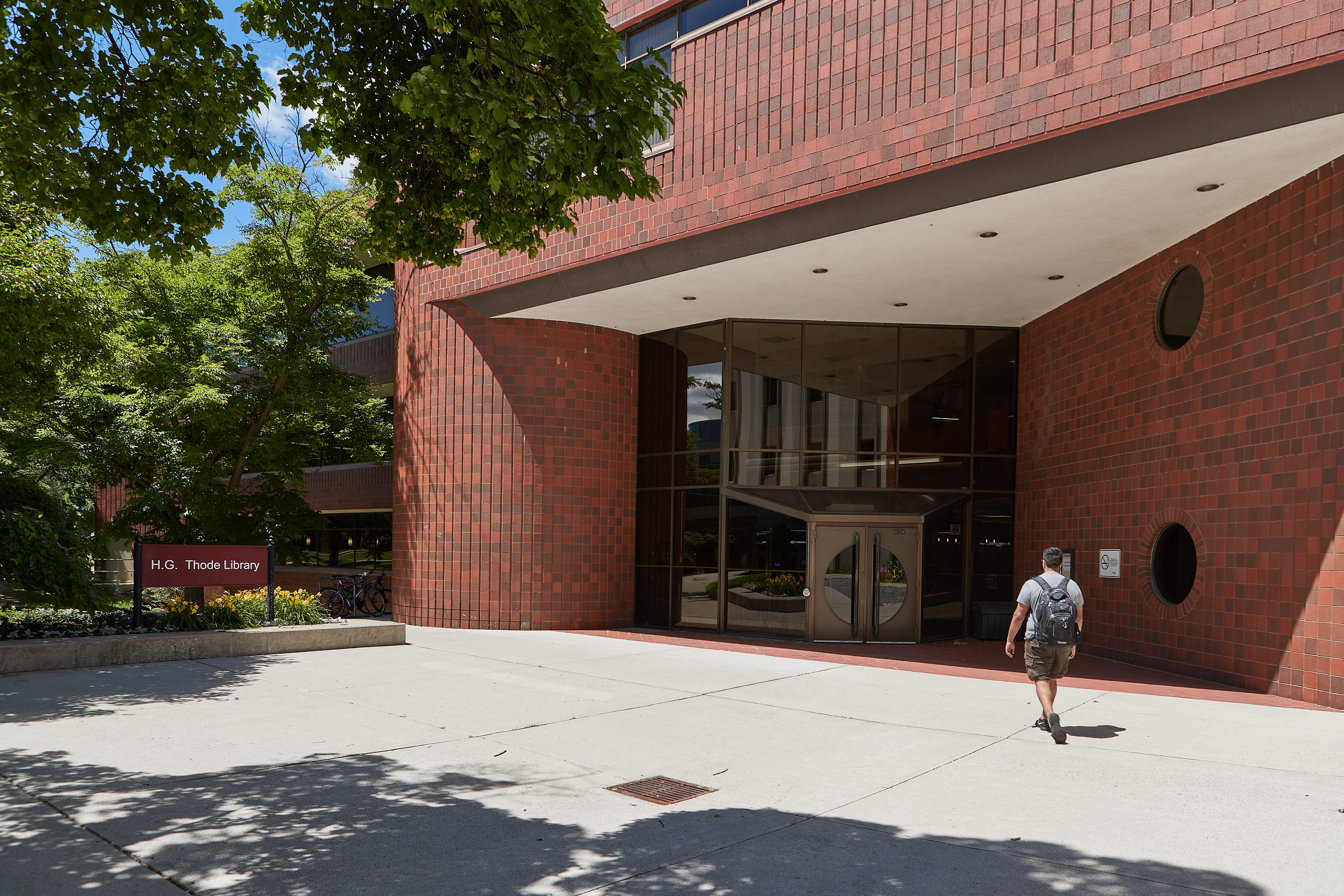 """Photo of a student walking into a red brick building with sign reading """" H.G. Thode Library"""""""