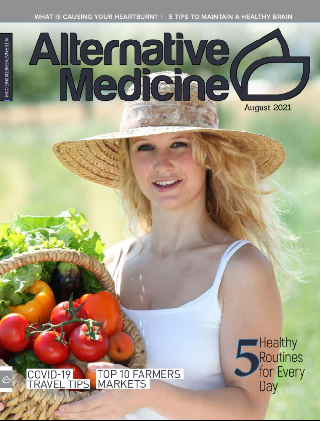 White feminine presenting person wearing a large brimmed hat and holding a basket of vegetables.